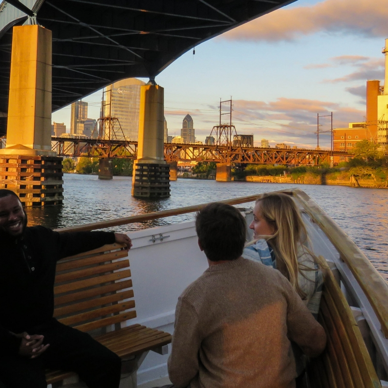View of Philadelphia from a boat under the 1-76 bridge at sunset